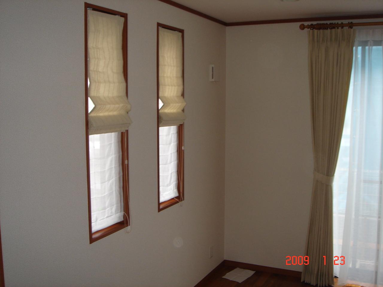 写真が暗いのですがリビングです。<br>開放感有るリビングをとの狙いで壁紙は無地の織物調の飽きのこない物、カーテンは壁と同系色で広がり感を重視しました。